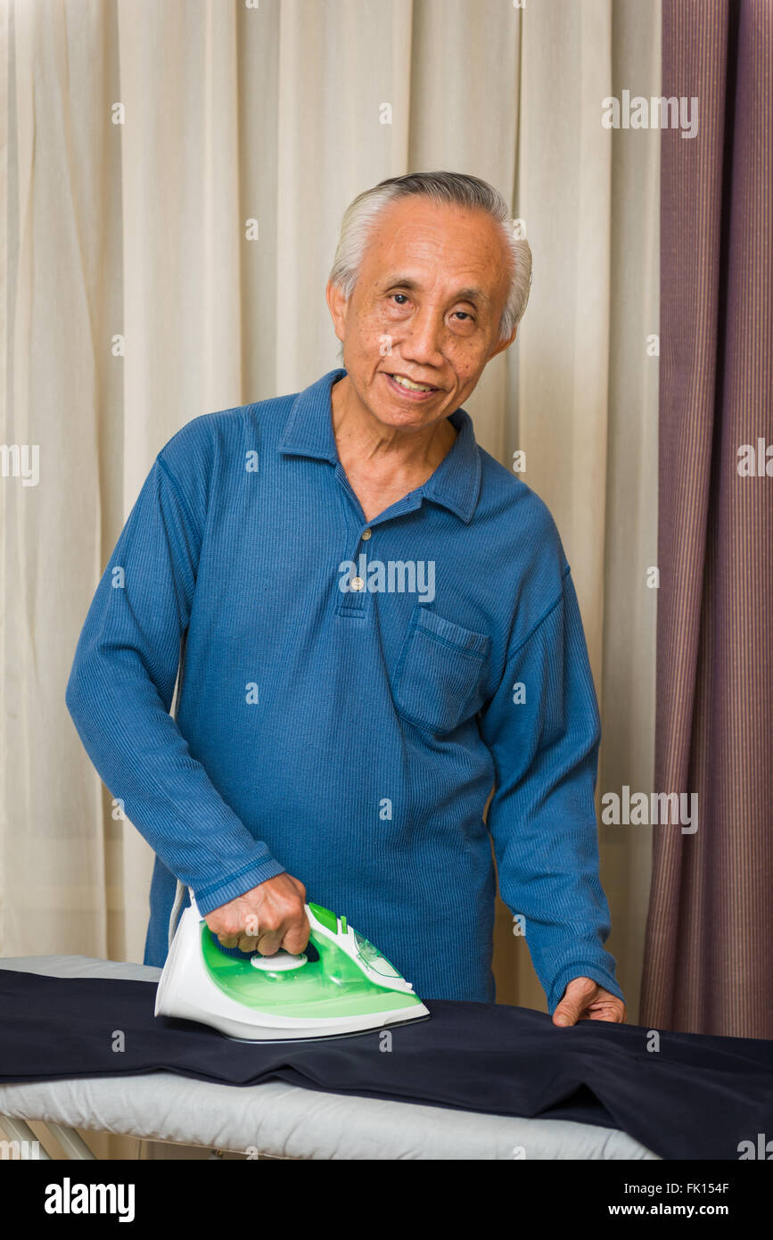 Happy Asian senior male enjoying doing housework. - Stock Image