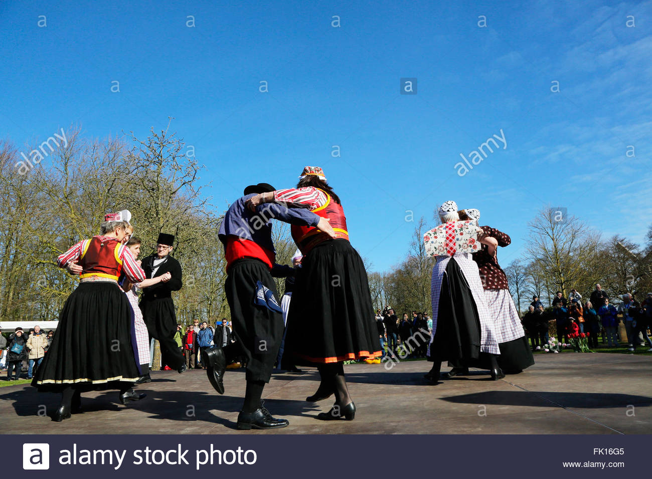 Elderly people in traditional Dutch costumes are dancing in