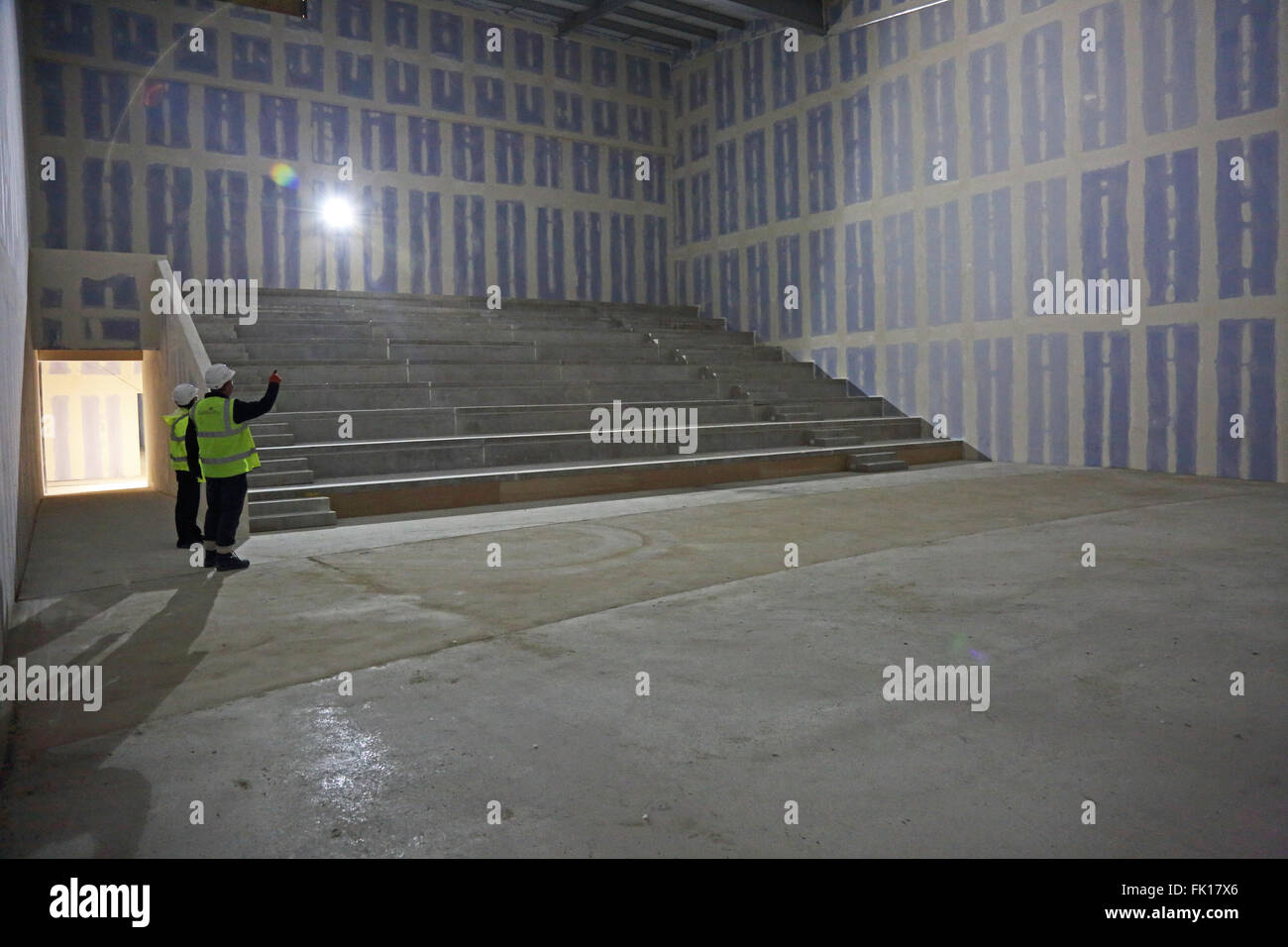 Two construction workers inspect the partly finished shell of a new cinema being constructed in London, UK - Stock Image