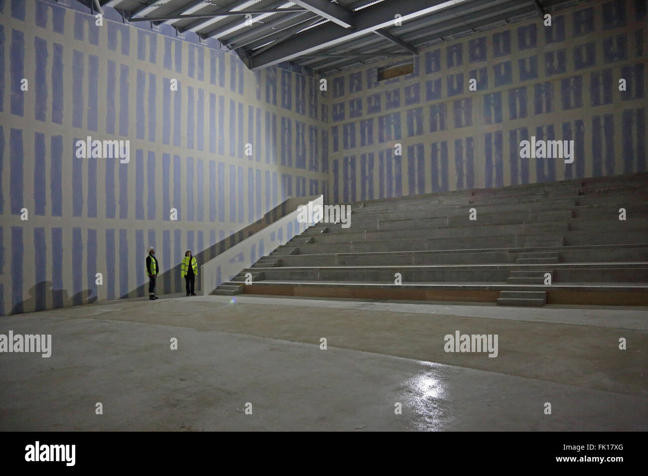 A male and female construction worker inspect the partly finished shell of a new cinema being constructed in London, - Stock Image