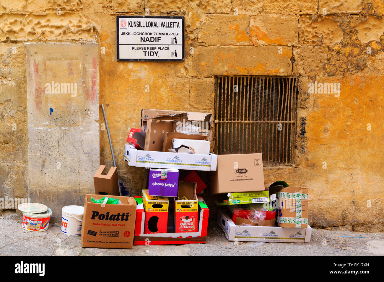 Sign asking to keep tidy on wall above pile of empty boxes and rubbish, Valletta, Malta. - Stock Image