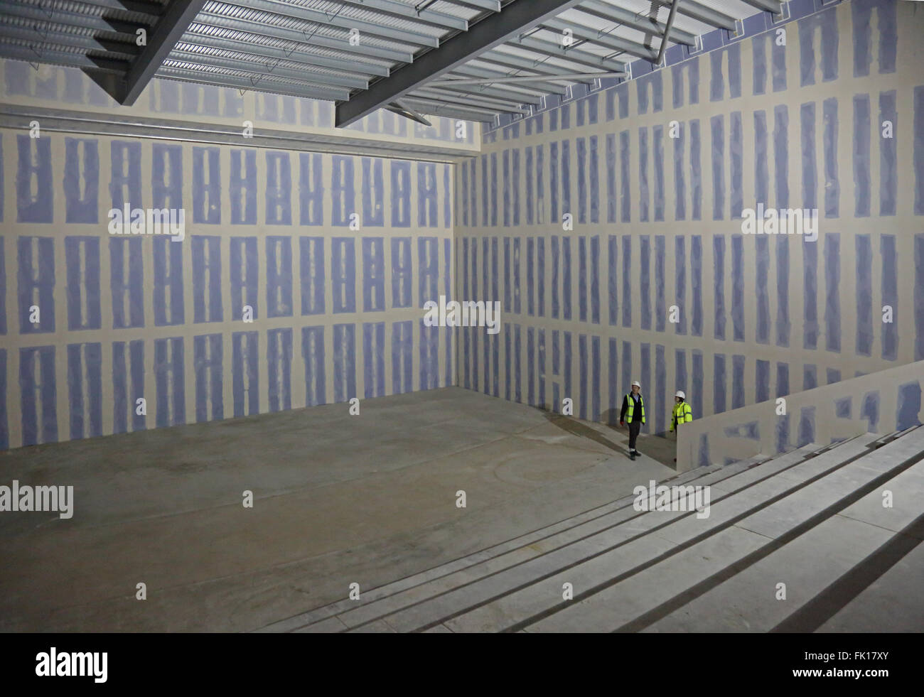 Two workers inspect the partly finished shell of a new cinema being constructed in London, UK - Stock Image