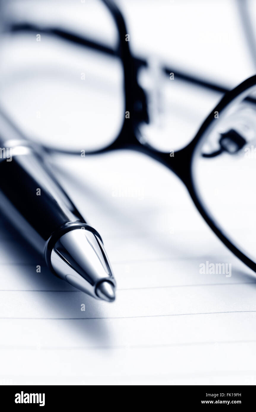 Ballpoint pen and prescription eyeglasses on lined notebook paper - Stock Image