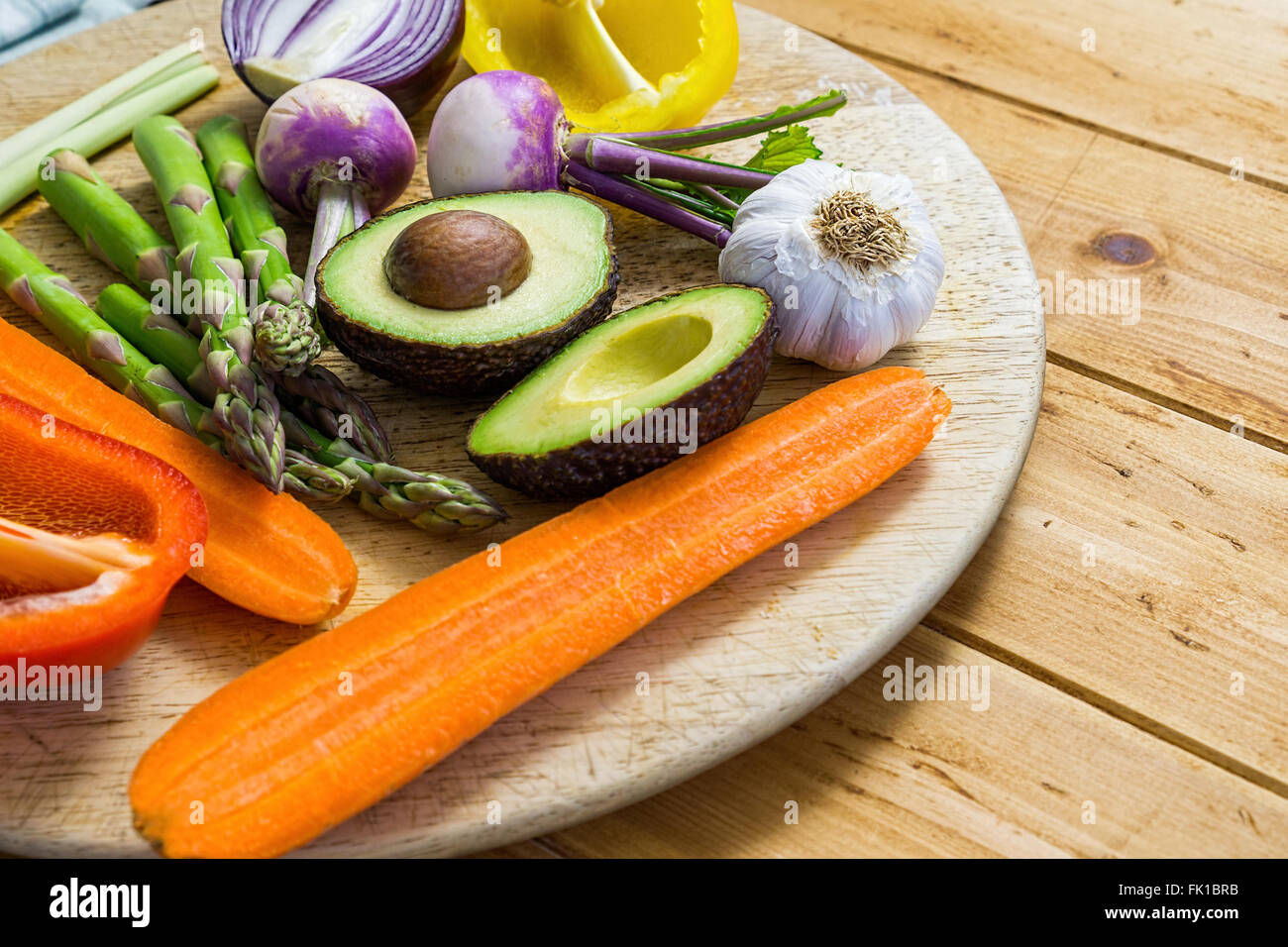 Mix of fresh vegetables sliced on a wooden table, flatly, asparagus avocado, bell peppers, onion - Stock Image