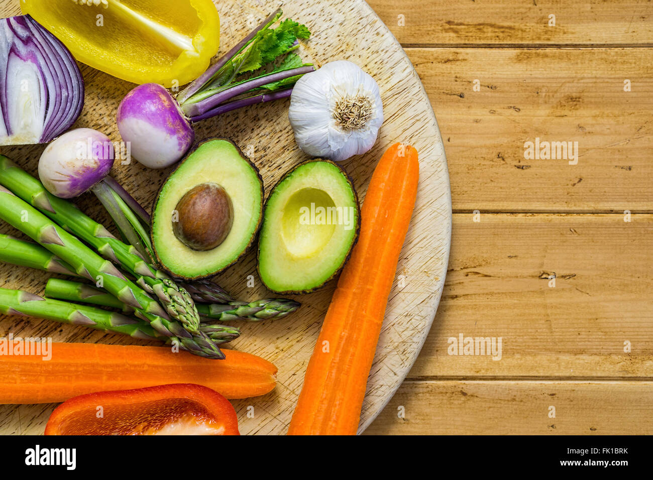 Fresh vegetables sliced in half on a wooden table, flatly, asparagus avocado, bell peppers, onion, space for text - Stock Image