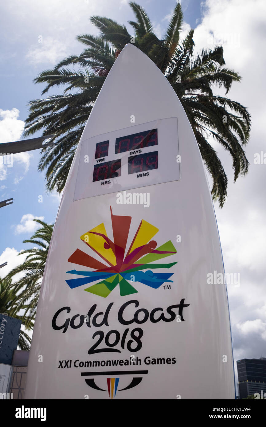 A sign in the shape of a surfboard showing the time remaining until the 2018 Commonwealth Games commence in Gold - Stock Image