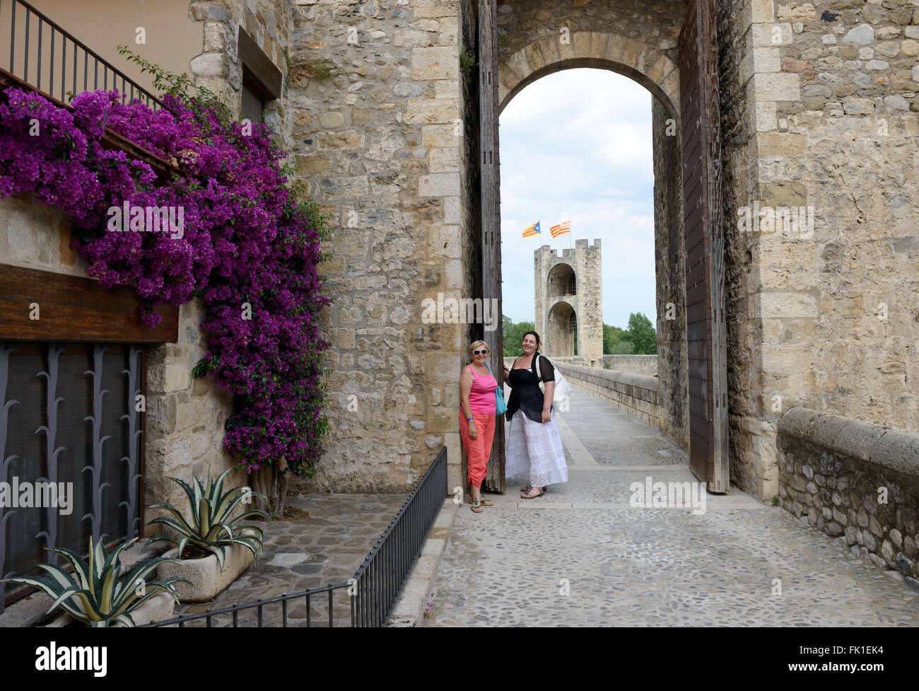 Senior smiling mother and her middle adult daughter are posing on background of western gate to Old Bridge of medieval Stock Photo
