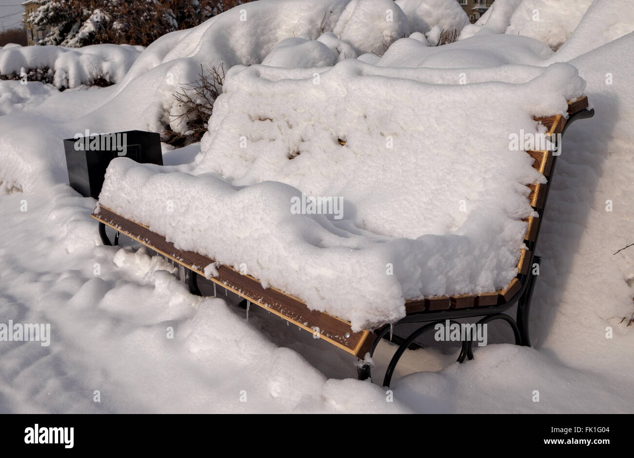 Snowdrift on bench after heavy snowfall - Stock Image