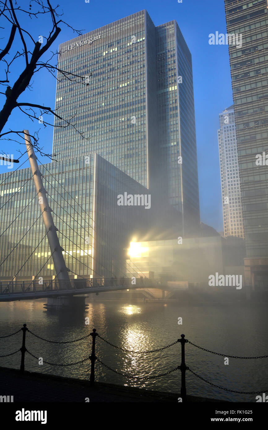 JP Morgan tower block rising above winter fog clearing from Canary Wharf waterways with sun reflecting on glazing - Stock Image