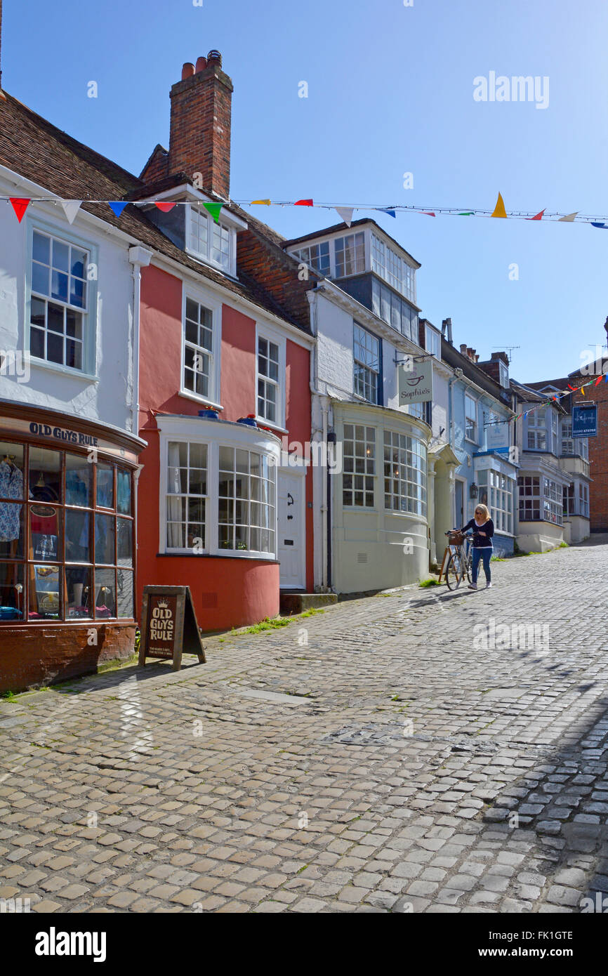 Lymington Hampshire colorful rendered walls and bay windows on shopfronts along hilly cobbled Quay Hill street in - Stock Image