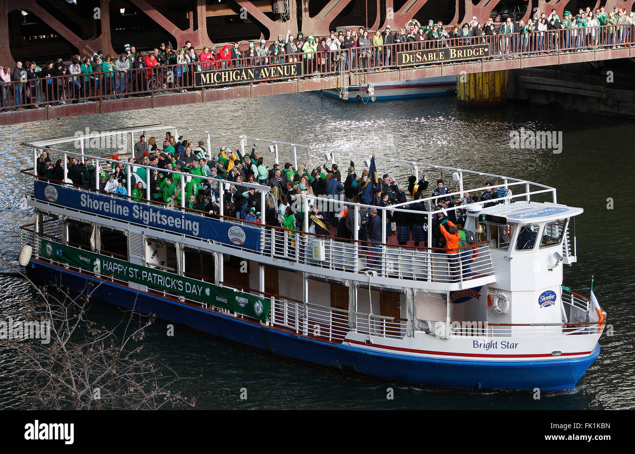 A tour boat sails under the DuSable Bridge across Michigan Avenue on the Chicago River during the St. Patrick's - Stock Image