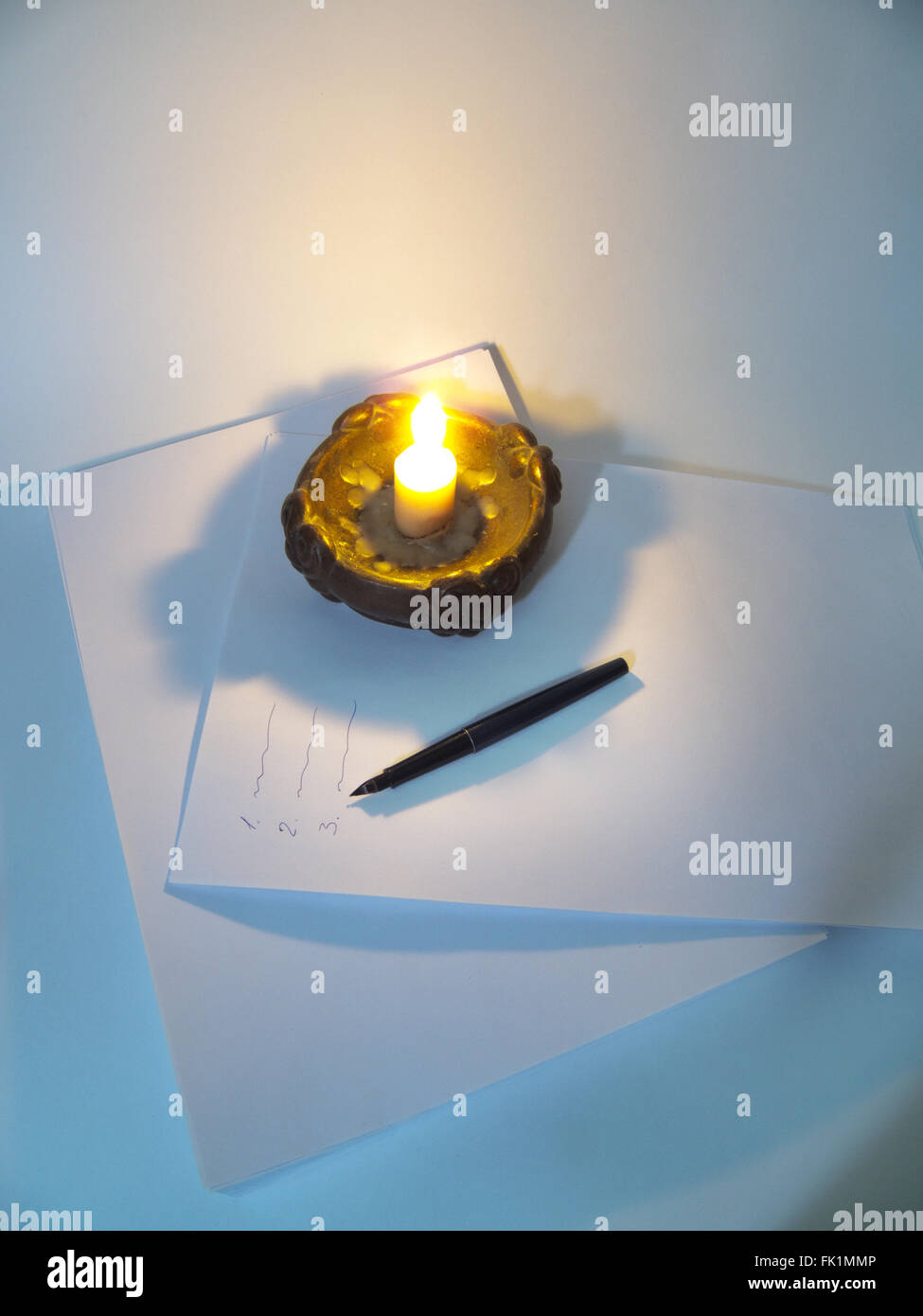 candle, feather pen on the stack of paper with inscriptions - Stock Image