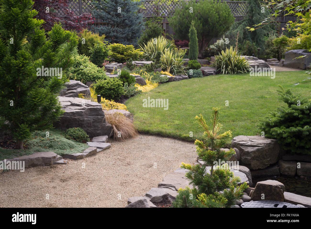 Sand Backyard a sand pebbled path leads to a lush green backyard lawn featuring