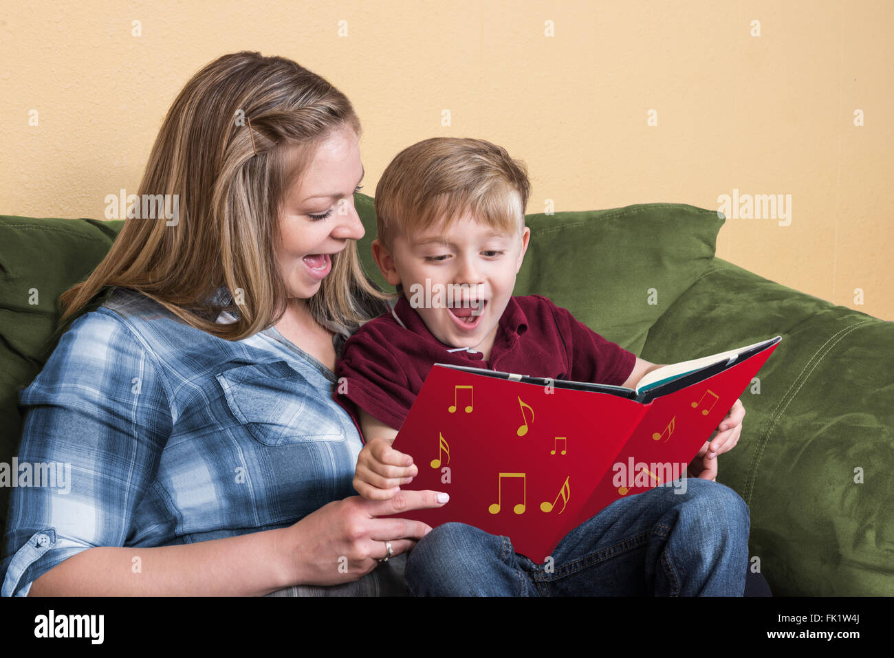 A young child gets ready to read by singing with his mother using a