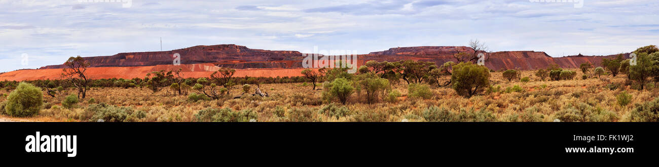 wide horizontal panorama of open pit iron ore mine in South Australia - Iron Knob town. - Stock Image