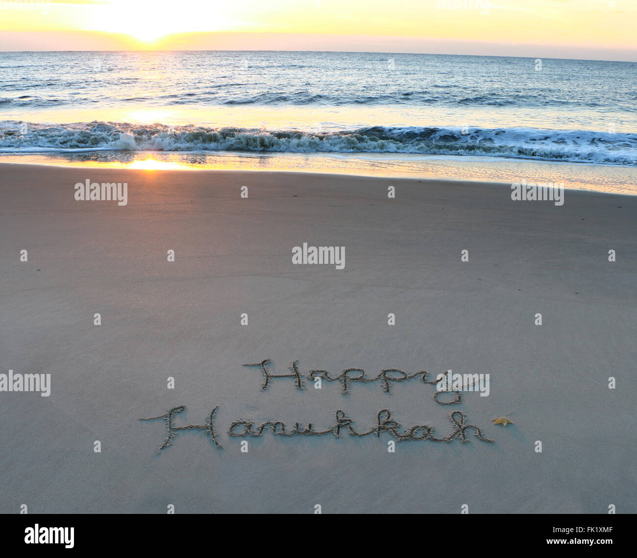 Happy Hanukkah written in sand on the beach Stock Photo