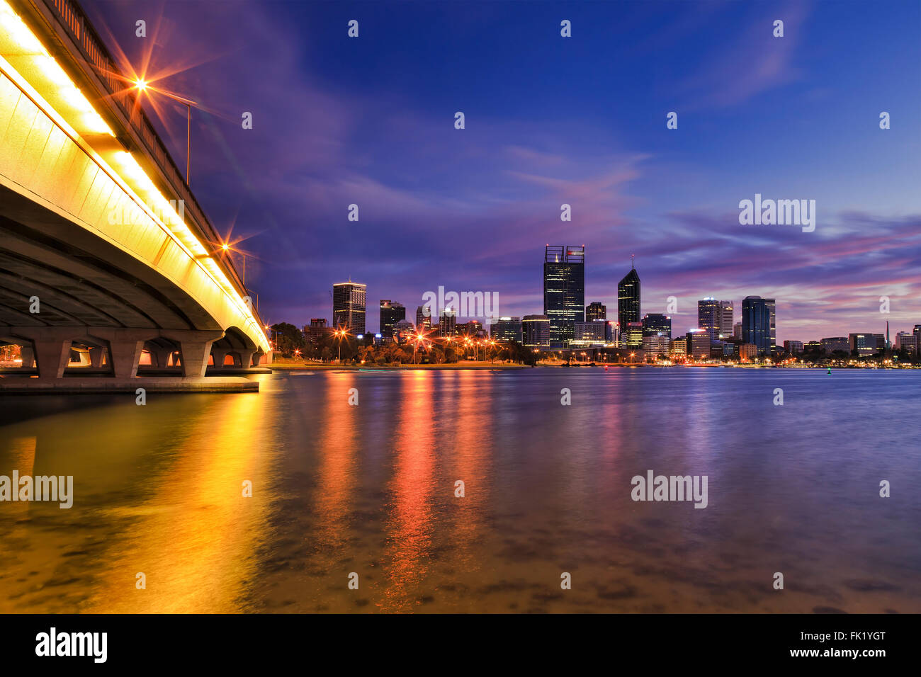 colourful sunrise over Perth city CBD with connecting bridge across Swan river. Bright lights reflecting in still - Stock Image