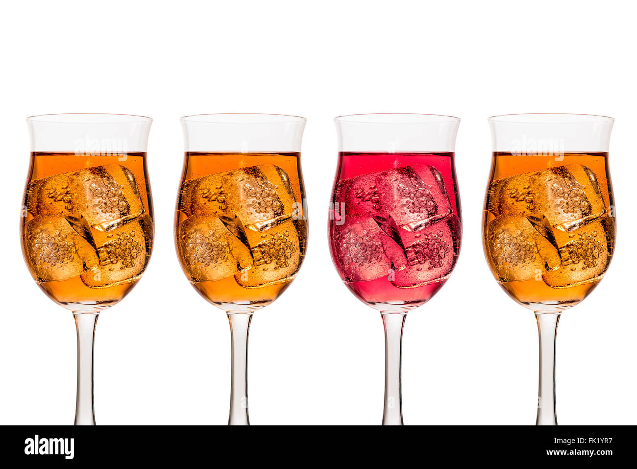 Four tall wine glasses containing amber and red coloured liquid wine and ice cubes shown with three amber and one - Stock Image