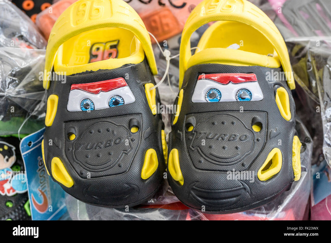 display clever novelty pair child's crocs designed to look like cars with pairs bright blue eyes staring out - Stock Image