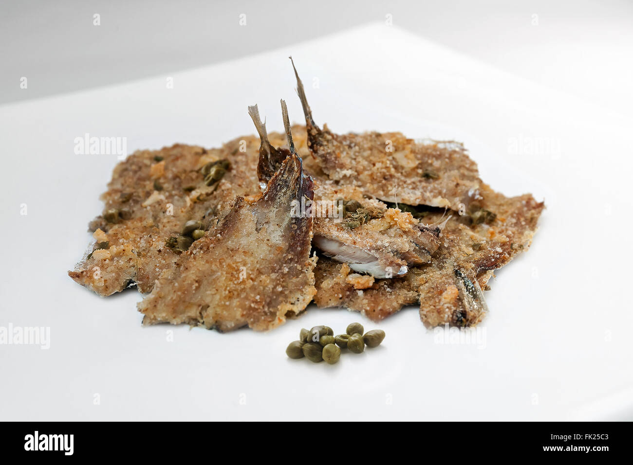 Anchovies baked with capers and breadcrumbs. Photographed in the studio, on the plate and a white background. - Stock Image