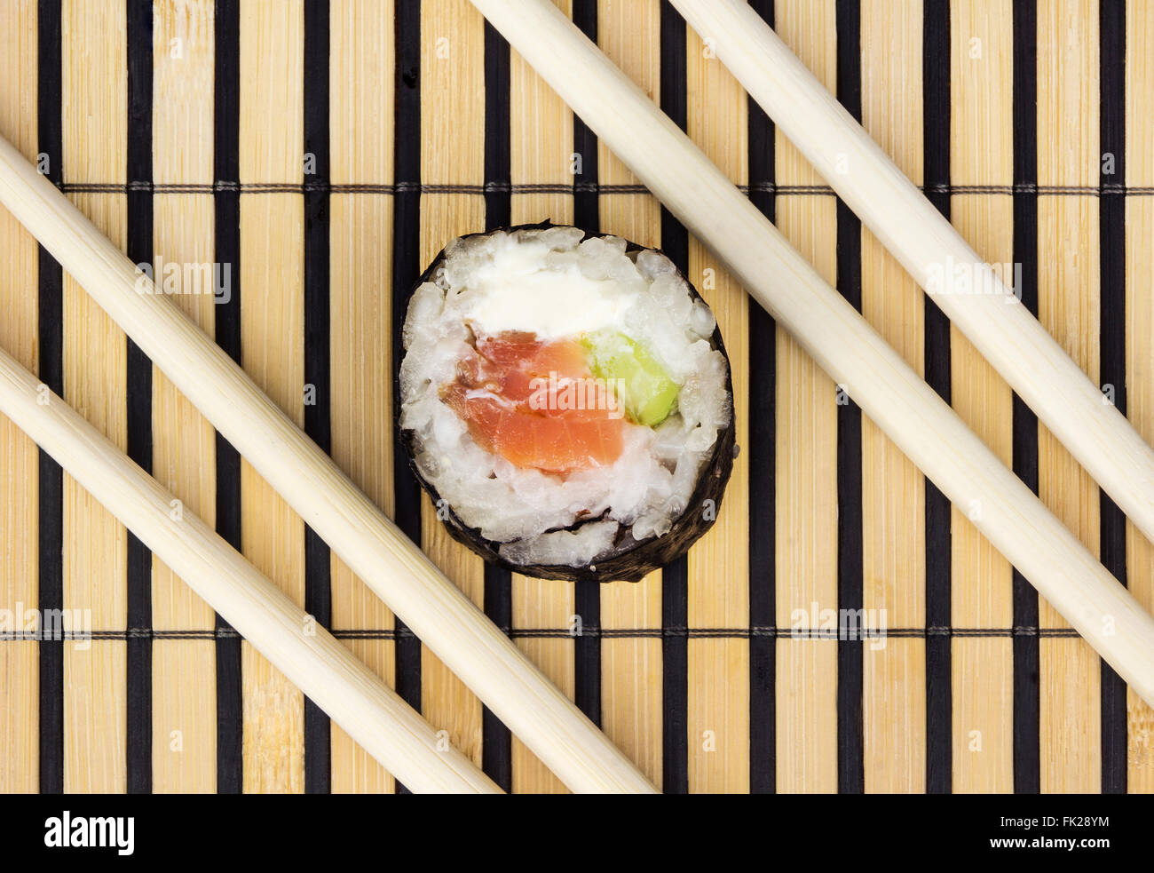 Sushi Roll And Chopsticks Over Bamboo Mat Stock Photo