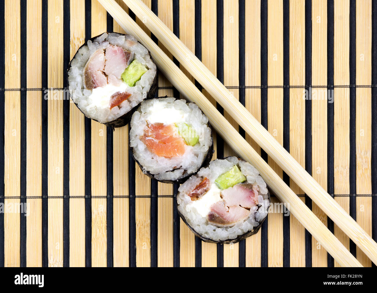 Three sushi rolls and chopsticks over bamboo mat - Stock Image