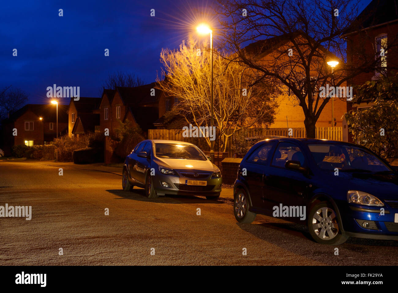 Cars parked on the side of a road at night - Stock Image