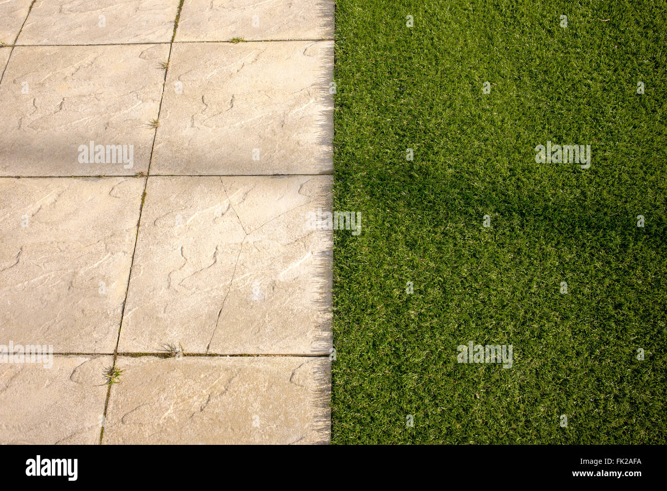 Artificial grass / astro turf meets paving slabs on a new build housing estate. Bicester, Oxfordshire, England Stock Photo