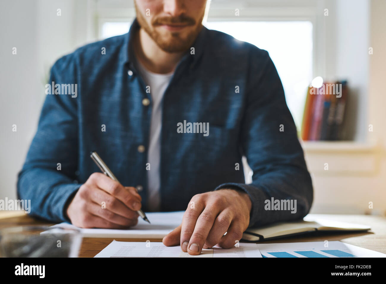 Cropped view of unidentifiable man in blue shirt with hand over paperwork as if to check statistics or plan something - Stock Image
