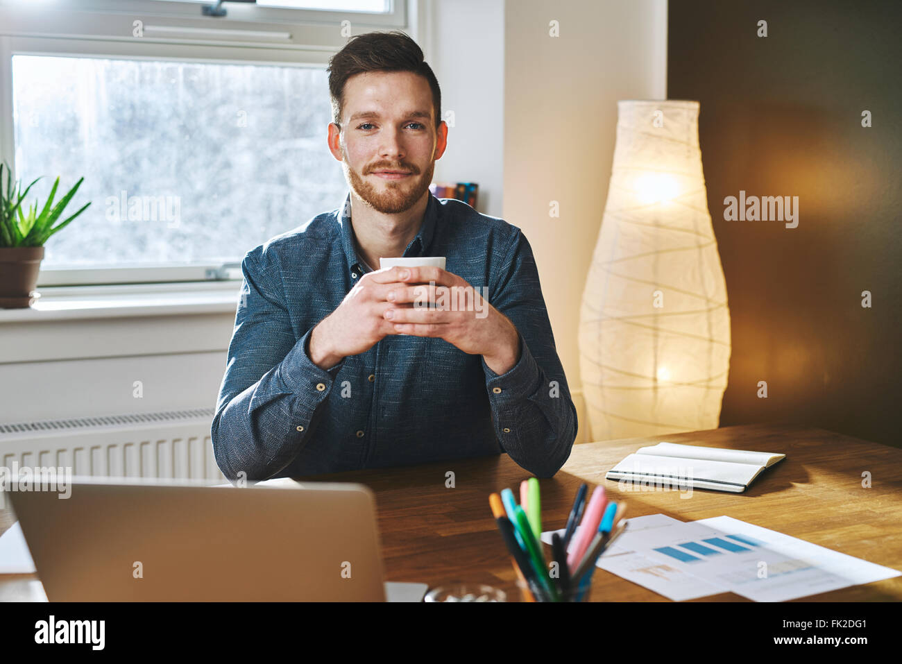 Young entrepreneur sitting in his office holding a cup of coffee smiling to the camera - Stock Image