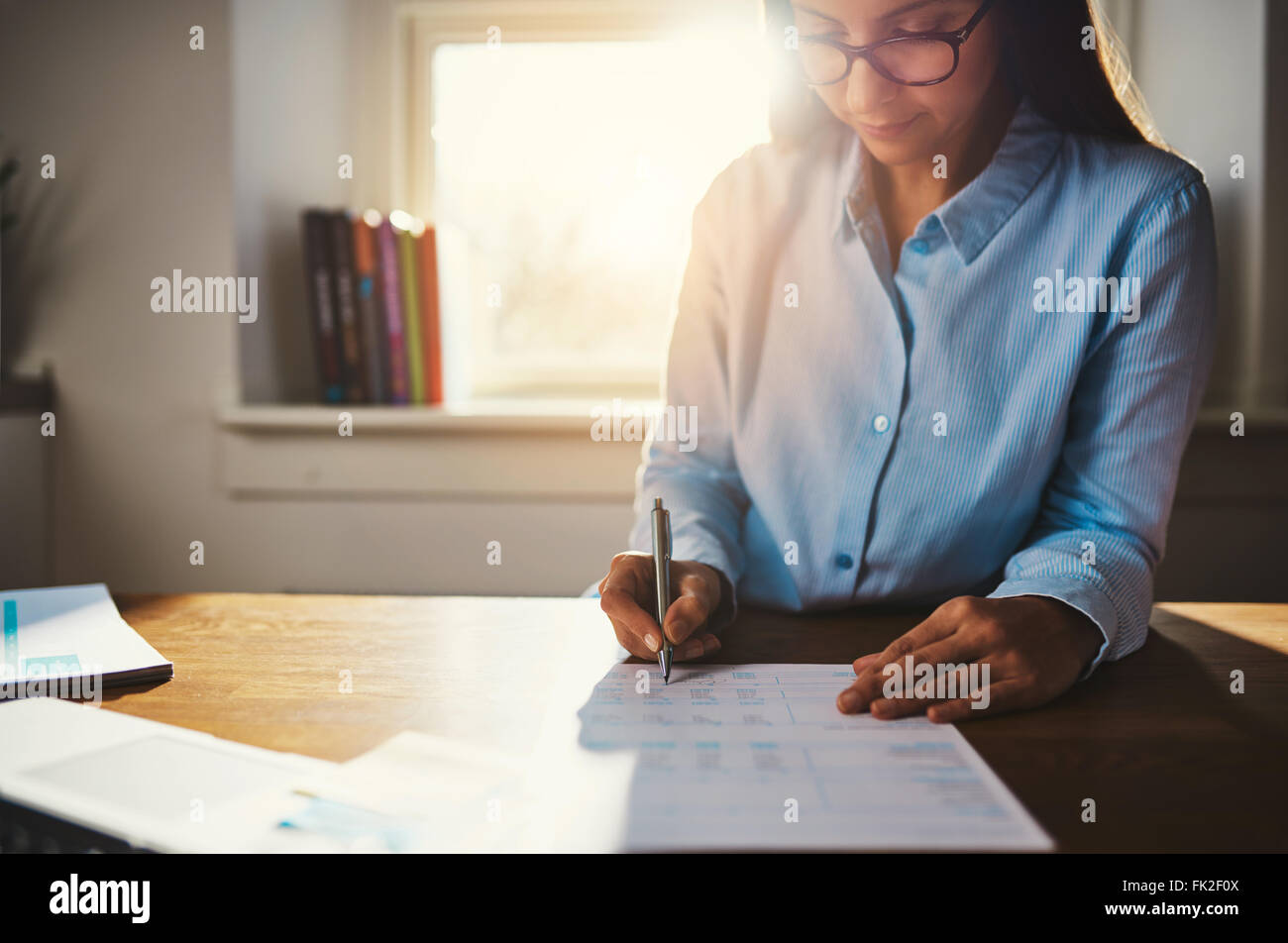 Single woman in blue blouse working at desk on paperwork in home office with sunlight over her shoulder through - Stock Image