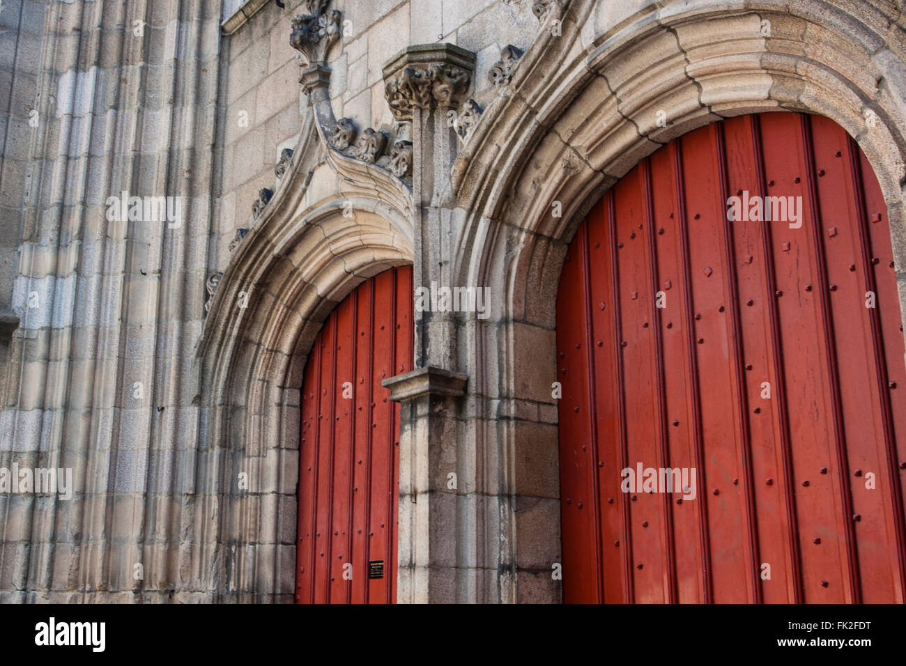 A pair of red doors marks the entrance to a church in Rennes - Stock Image