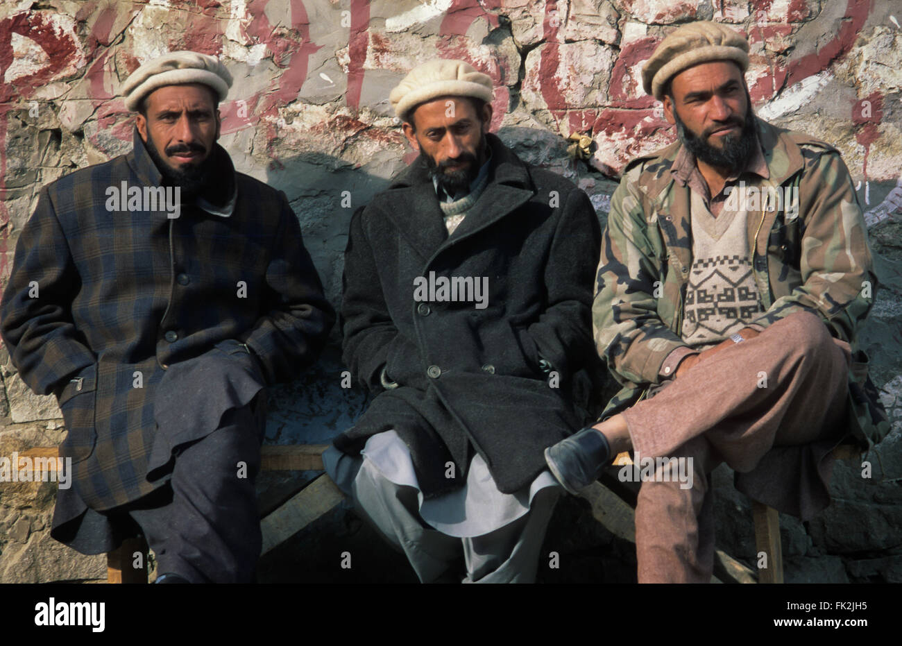 Three Pakistani men sitting on a bench in the village of Karimabad, Hunza Valley, Pakistan. - Stock Image