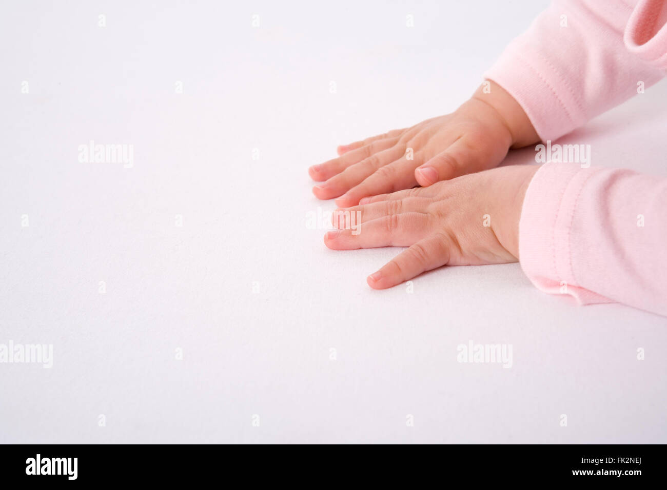 Baby hands on the floor on white background - Stock Image