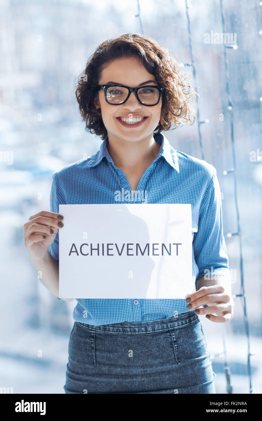 Smiling woman holding sheet of paper - Stock Image