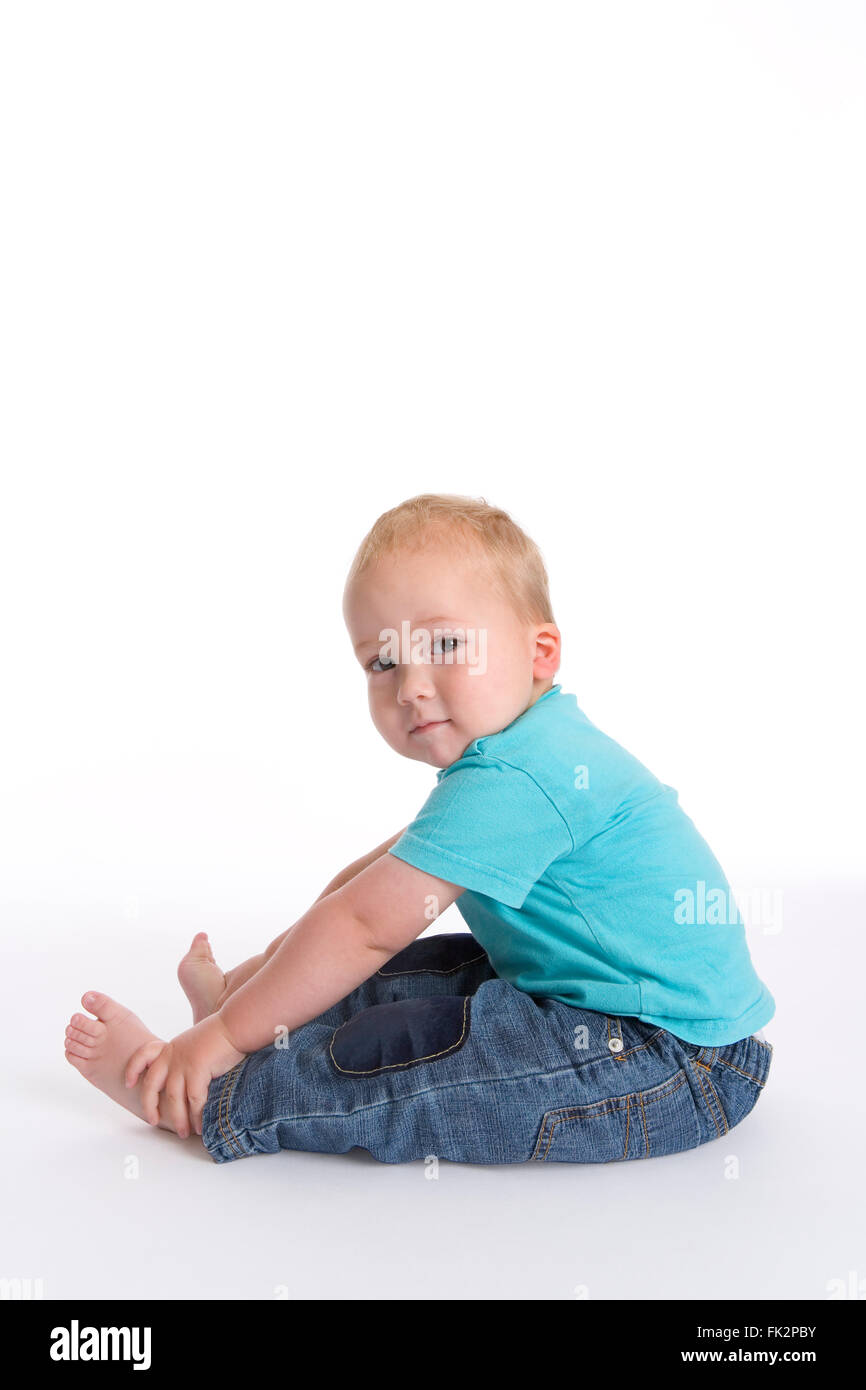 Toddler Boy Sitting On The Floor Holding His Feet Doing Fitness Excercise on white background - Stock Image