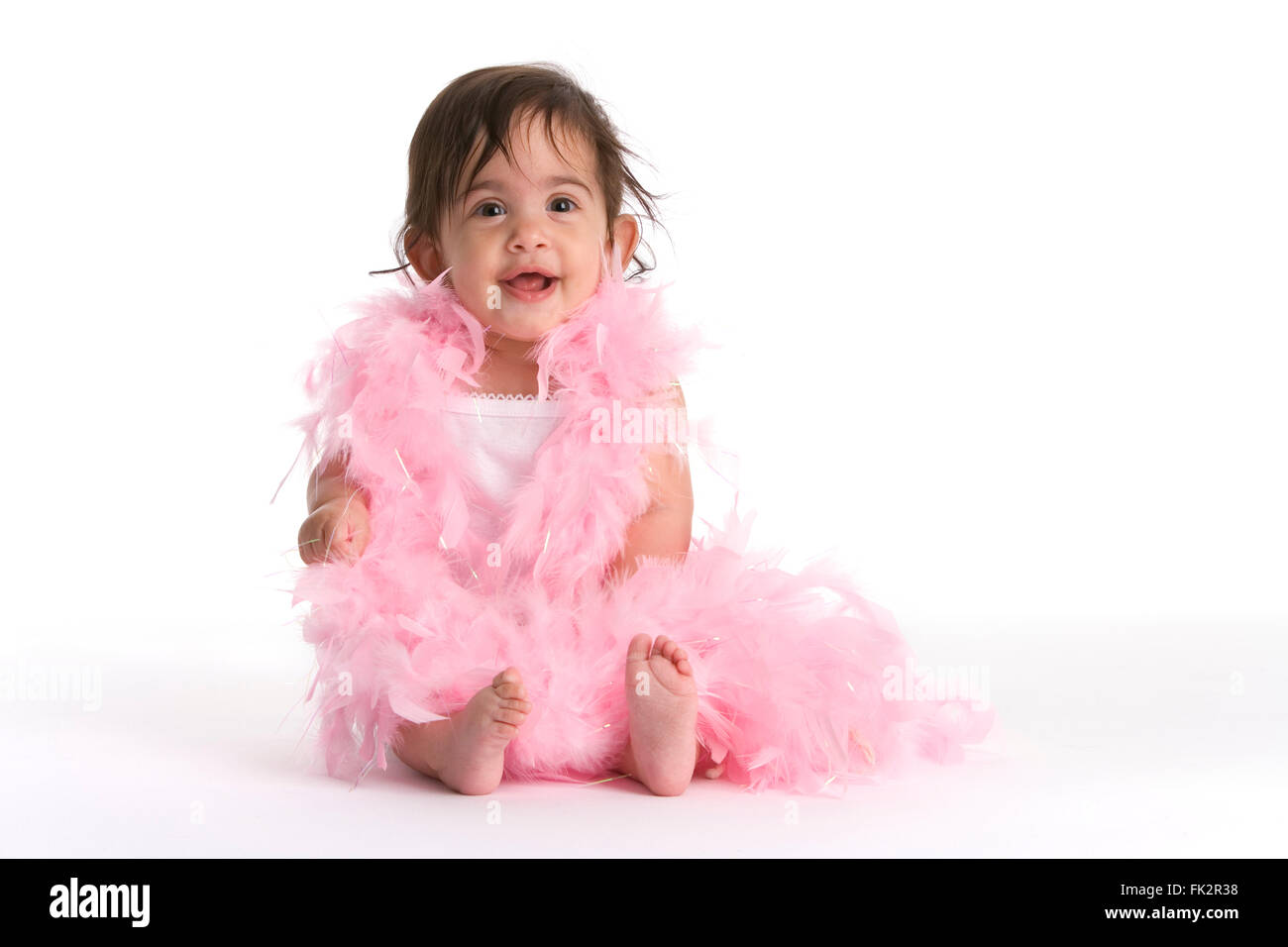 Baby Girl Sitting On The Floor Dressed In Pink Feathers Like A Diva on white background - Stock Image