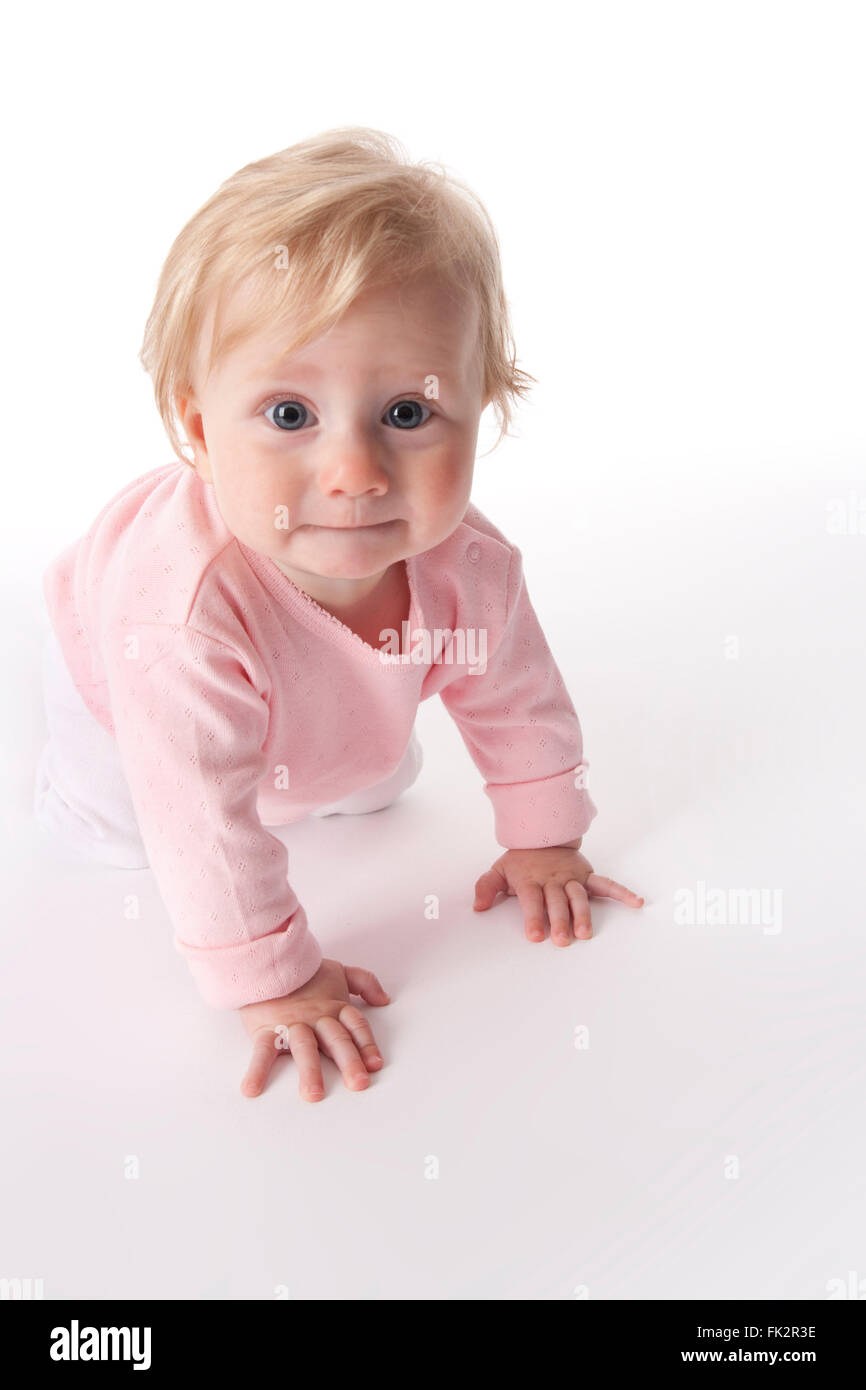 Baby girl is crawling on the floor and looks into the camera on white background - Stock Image