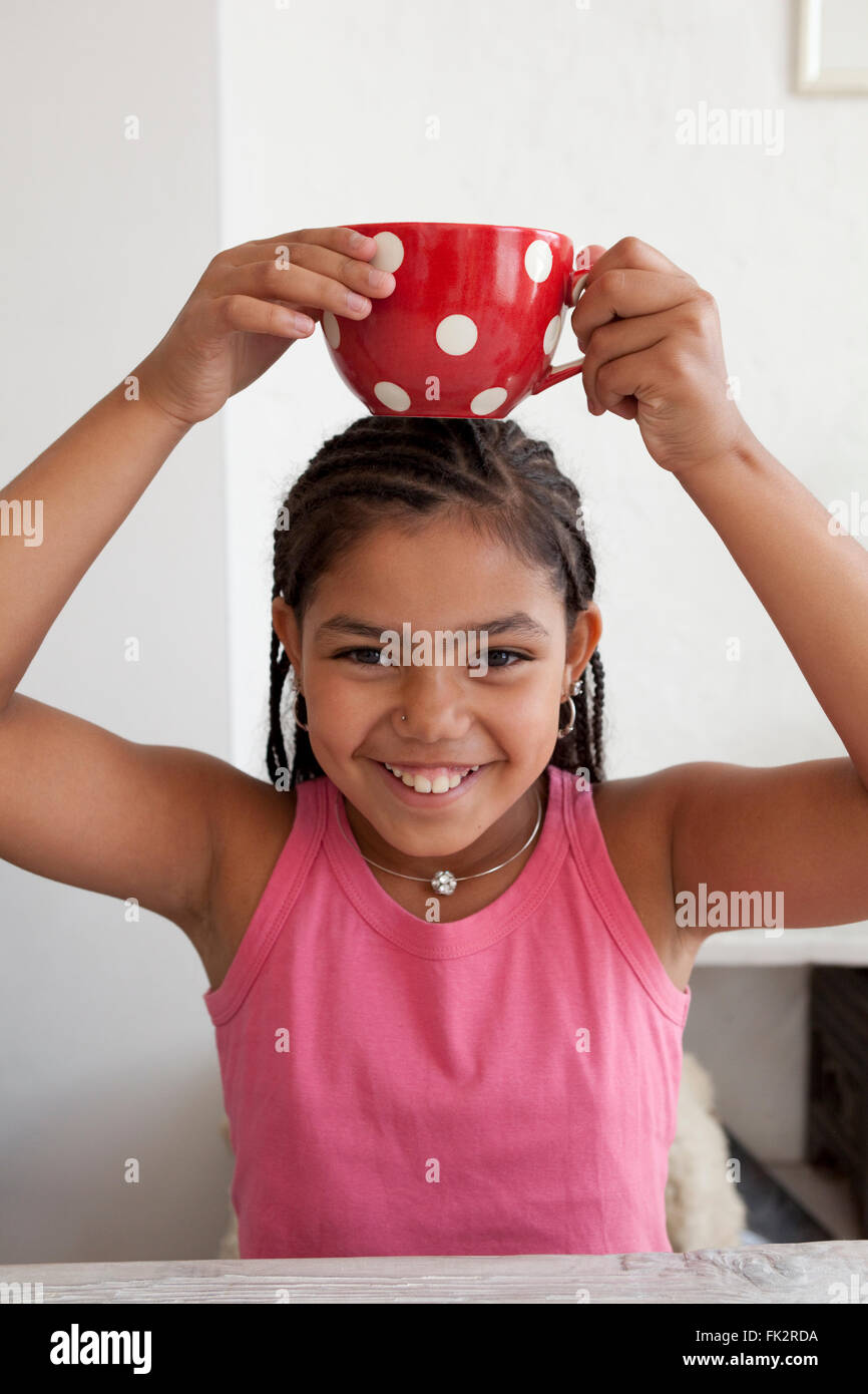 Little teenage girl is carrying a large cup on her head as a joke - Stock Image