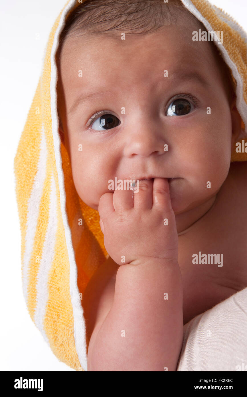 Portrait of a baby wrapped in a towel on white background - Stock Image