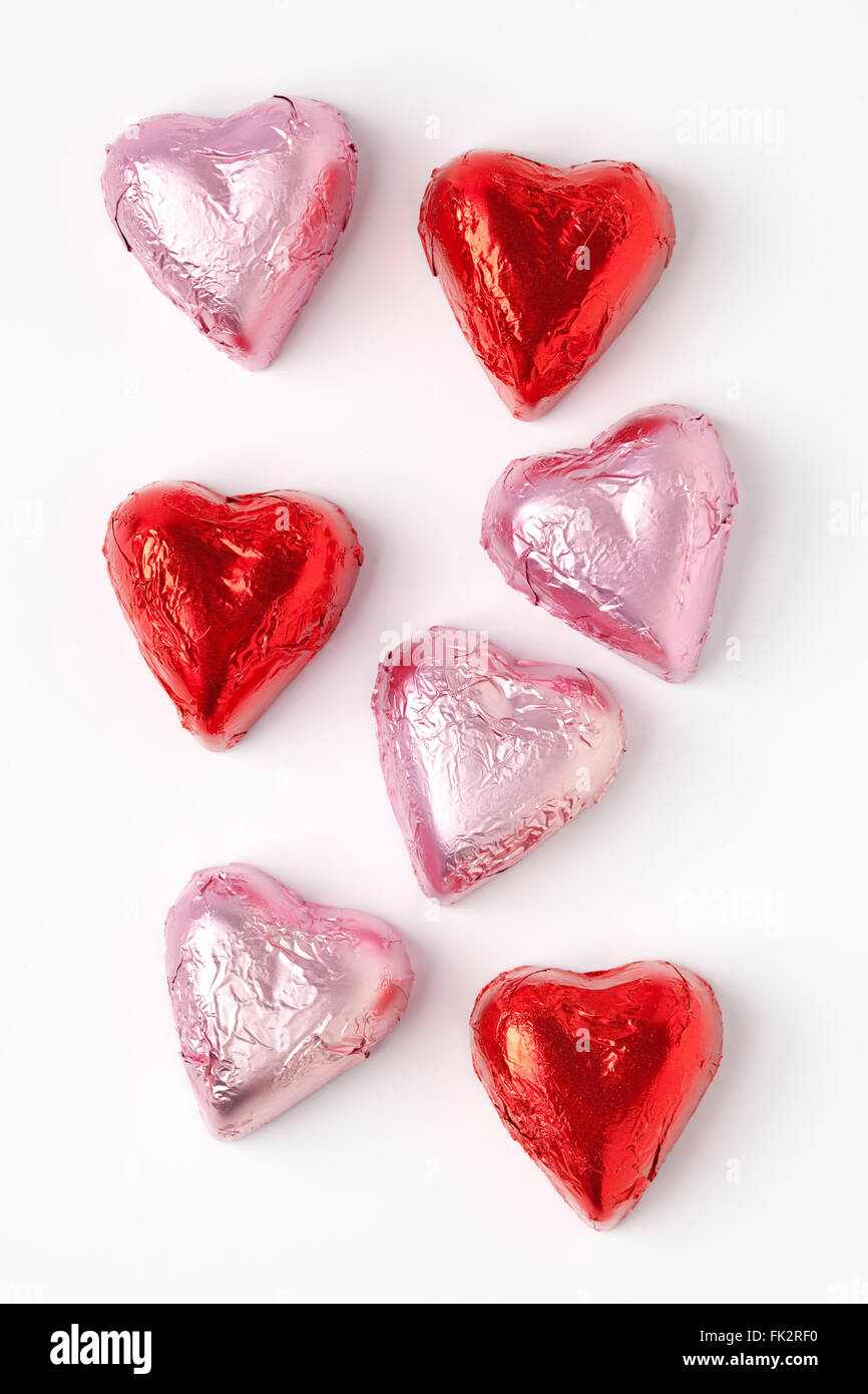 Chocolate hearts in pink and red tinfoil on white background - Stock Image