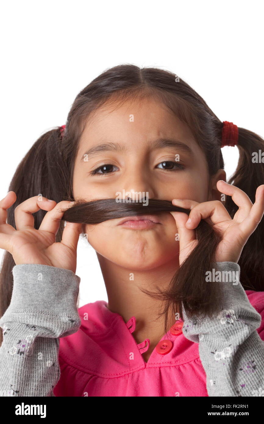 Little girl is making a moustache of her hair on white background - Stock Image