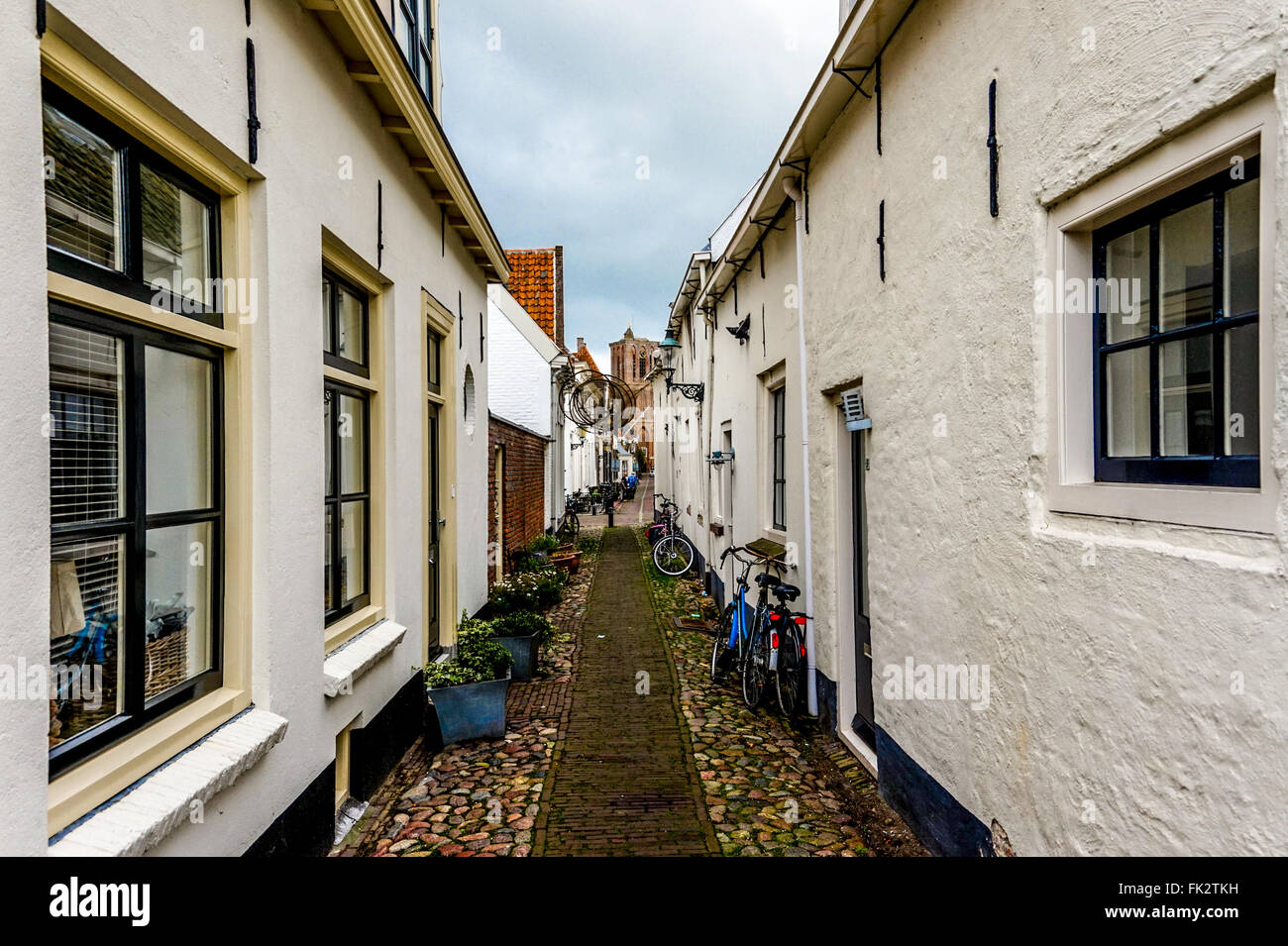 Bikes parked in a narrow street in the historic fishing village of Elburg in the Netherlands - Stock Image