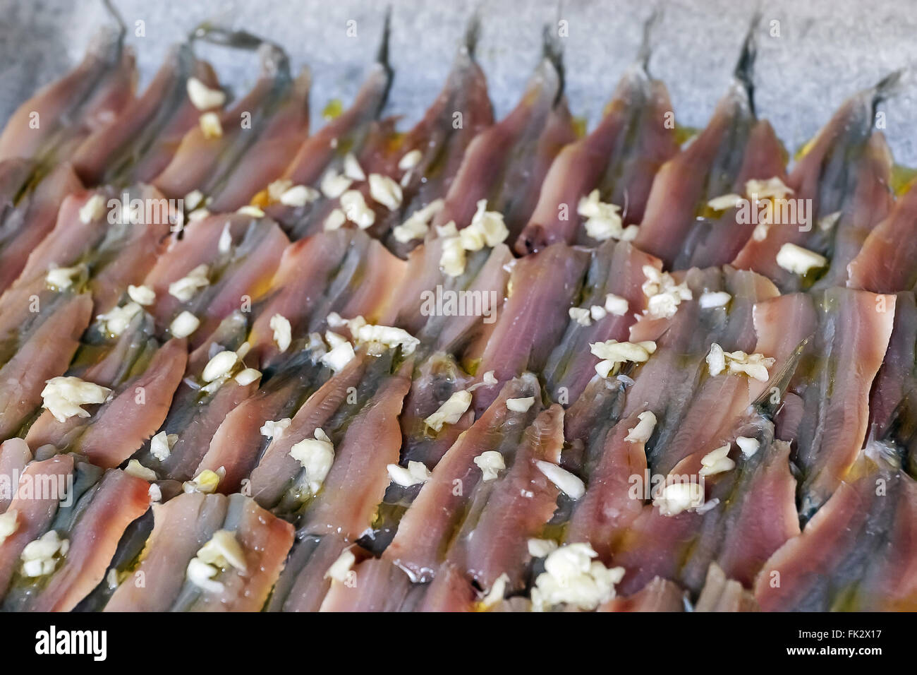 Raw anchovies prepared baking sheet and season before being fired and fired - Stock Image
