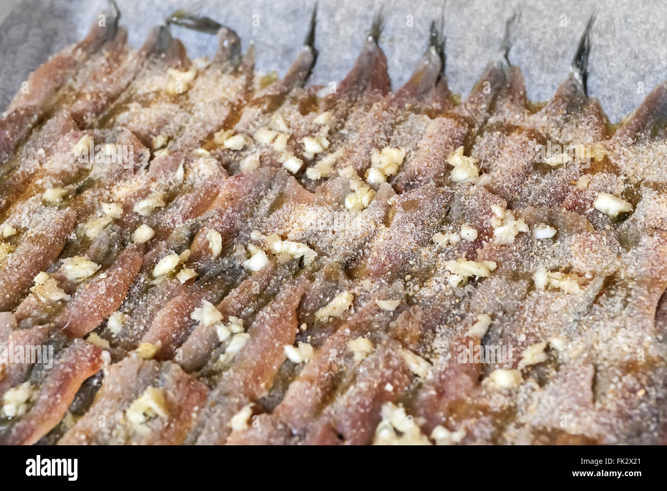 Raw anchovies prepared in pan with oil, garlic and breadcrumbs before being baked and cooked. - Stock Image