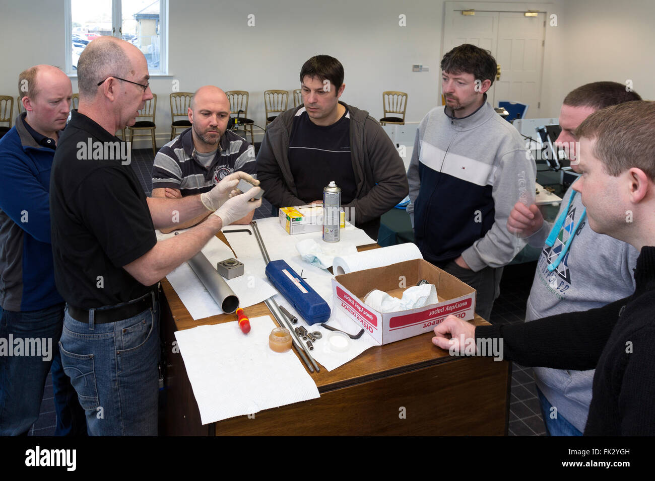 Adult men being taught engineering and pneumatics by qualified engineer instructor. - Stock Image