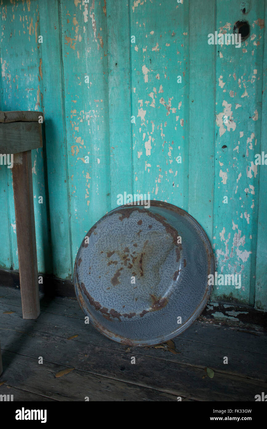 Rusted wash basin leans against the wall of a slave cabin behind a Louisiana plantation, USA. - Stock Image
