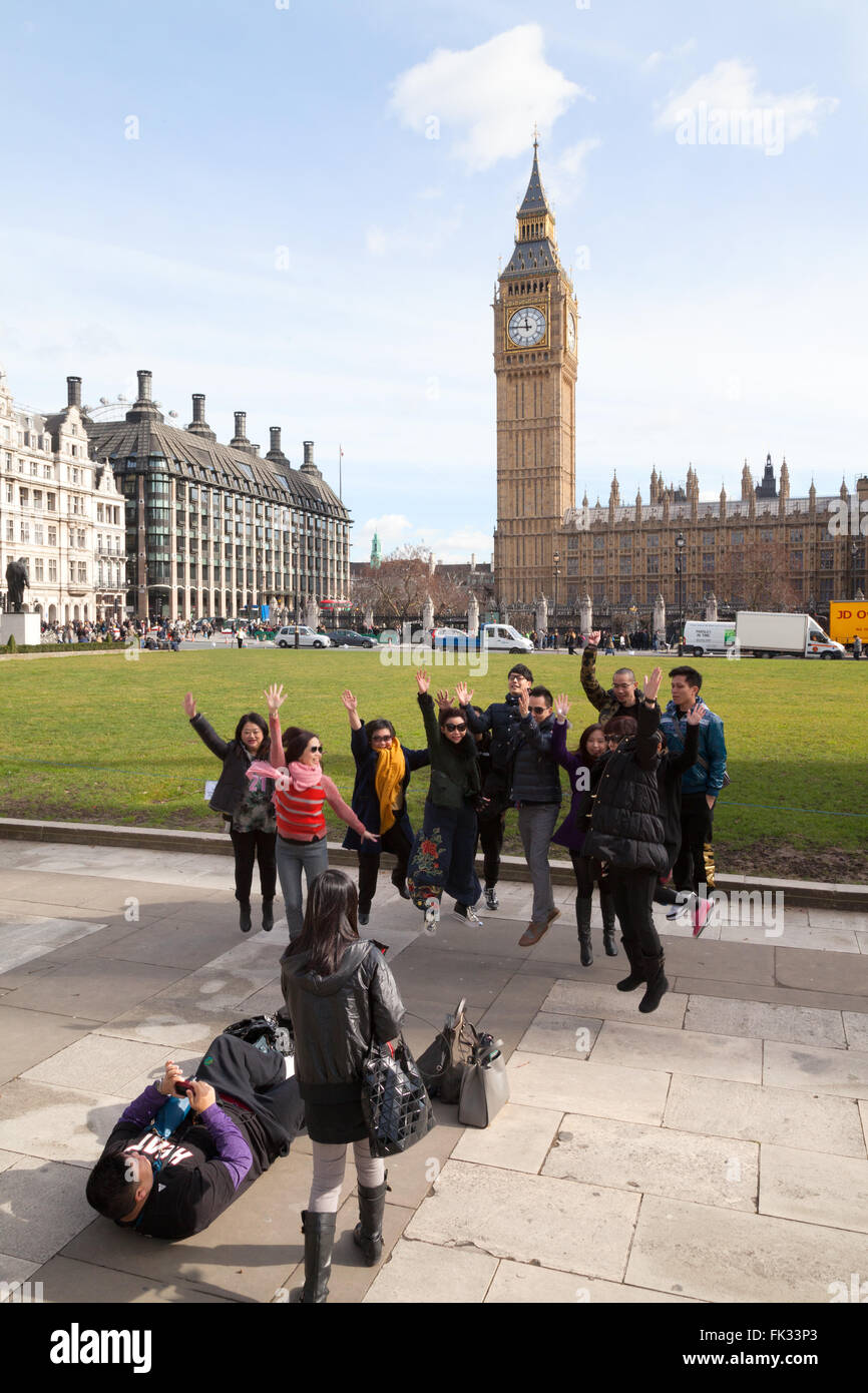 A group of Chinese tourists in London jumping in the air in front of Big Ben, Parliament Square London UK - Stock Image