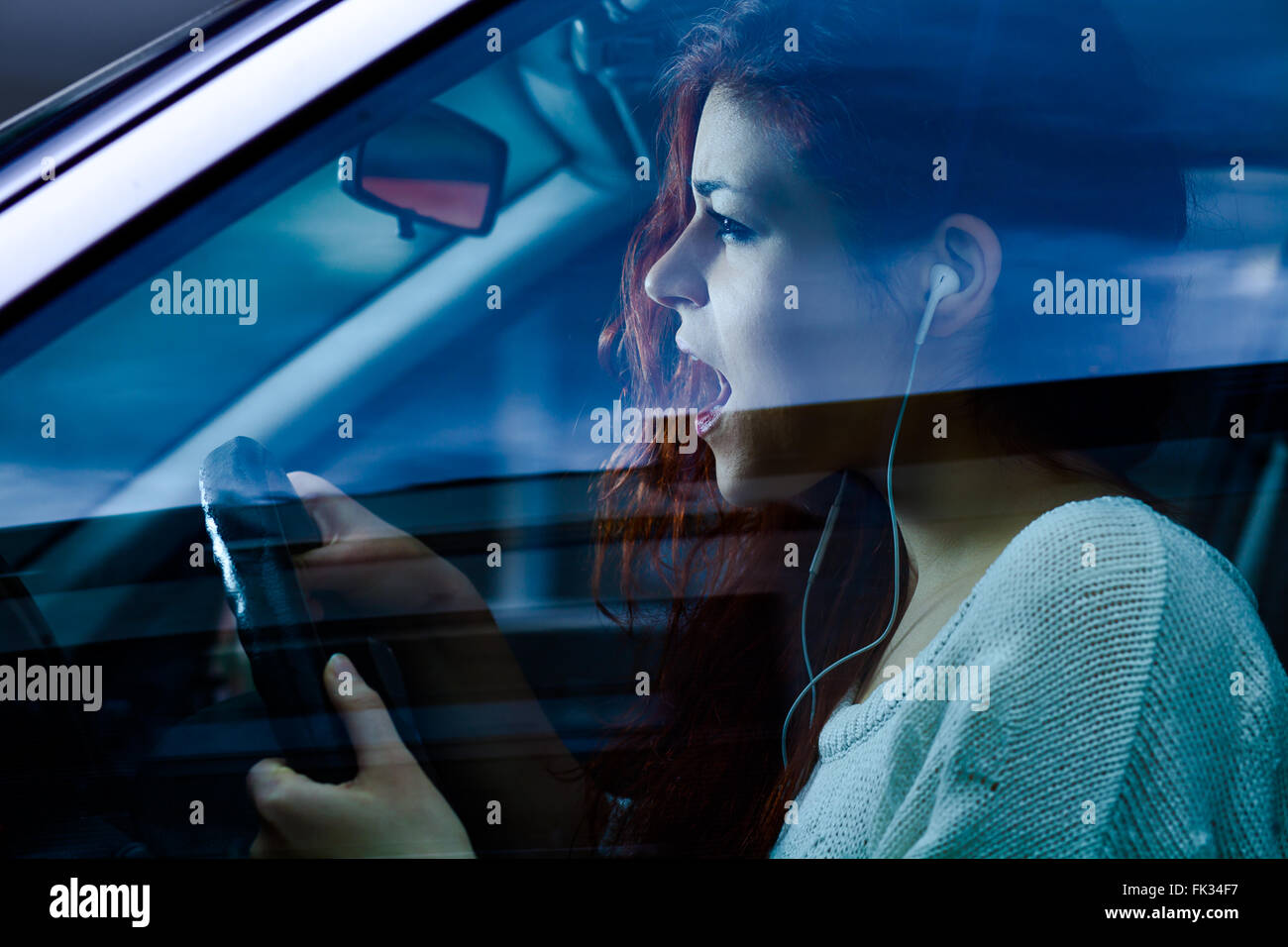 Screaming Woman with Earbuds Driving a Car - Stock Image