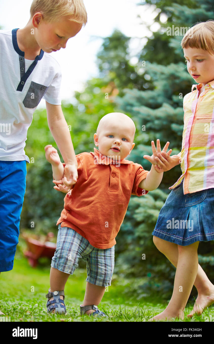 Two proud siblings helping baby to learn first steps in a garden - Stock Image